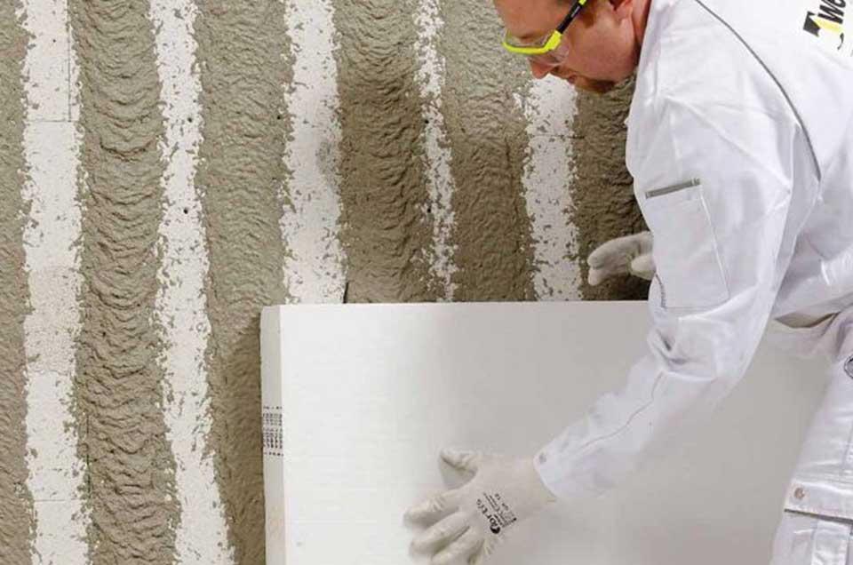Bild von einem Handwerker der eine Fassade dämmt